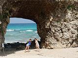 砂山ビーチの名物穴の前でポーズを決める女性