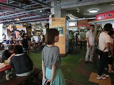 おんなの駅なかゆくい市場で食堂を選ぶ女性